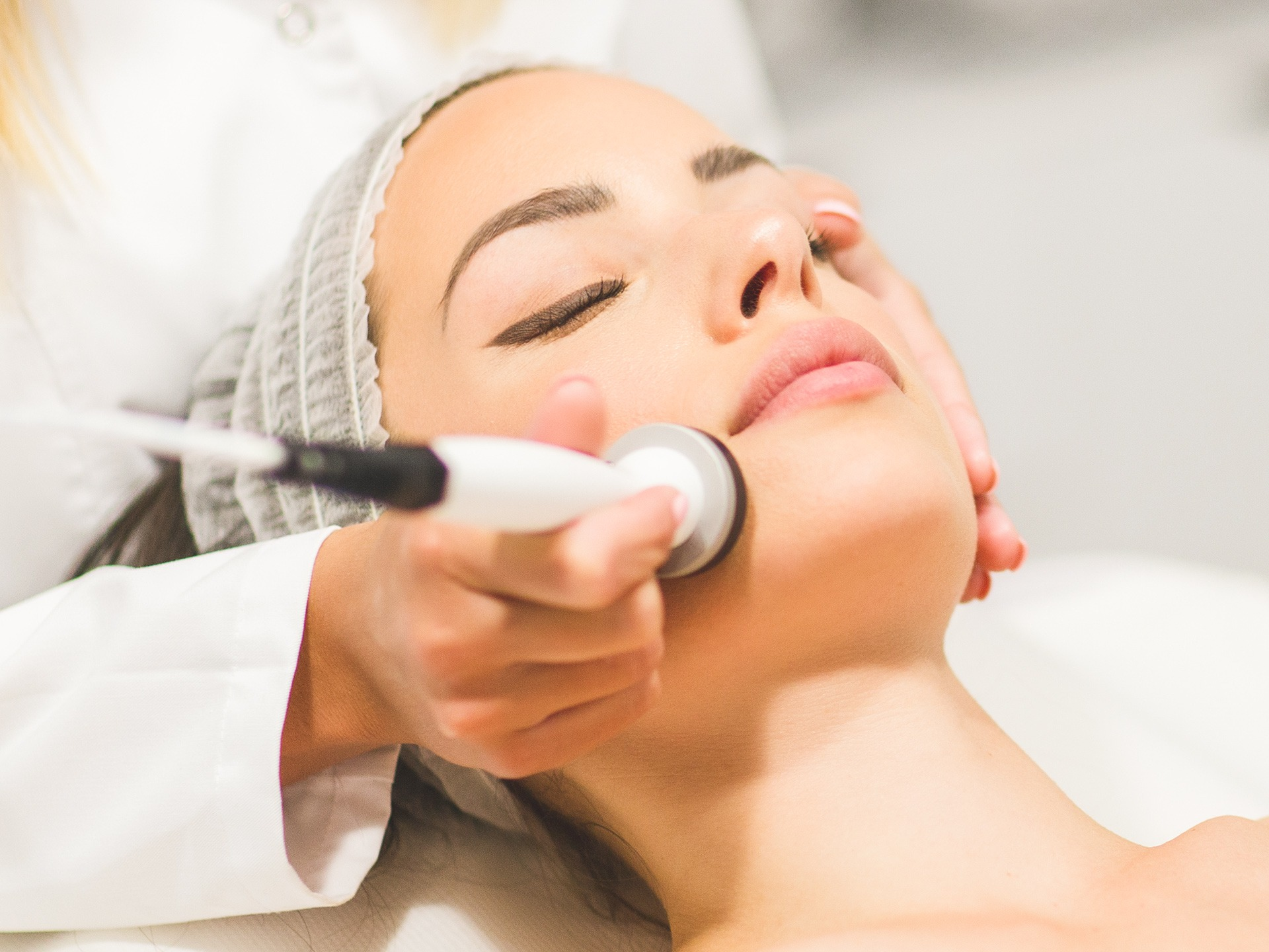 Beautiful young woman getting rejuvenating and tightening skin treatment at professional cosmetic salon.
