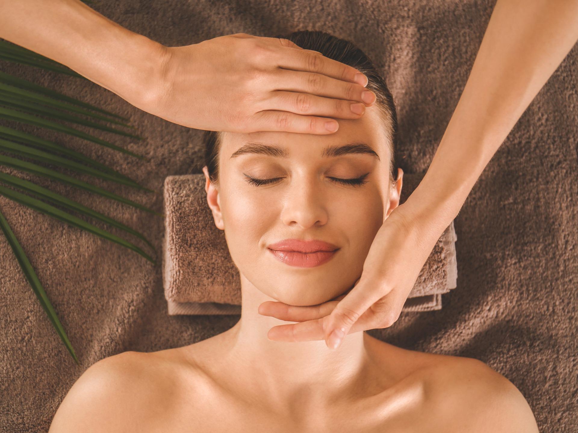 Beautiful young woman enjoying massage in spa salon, top view