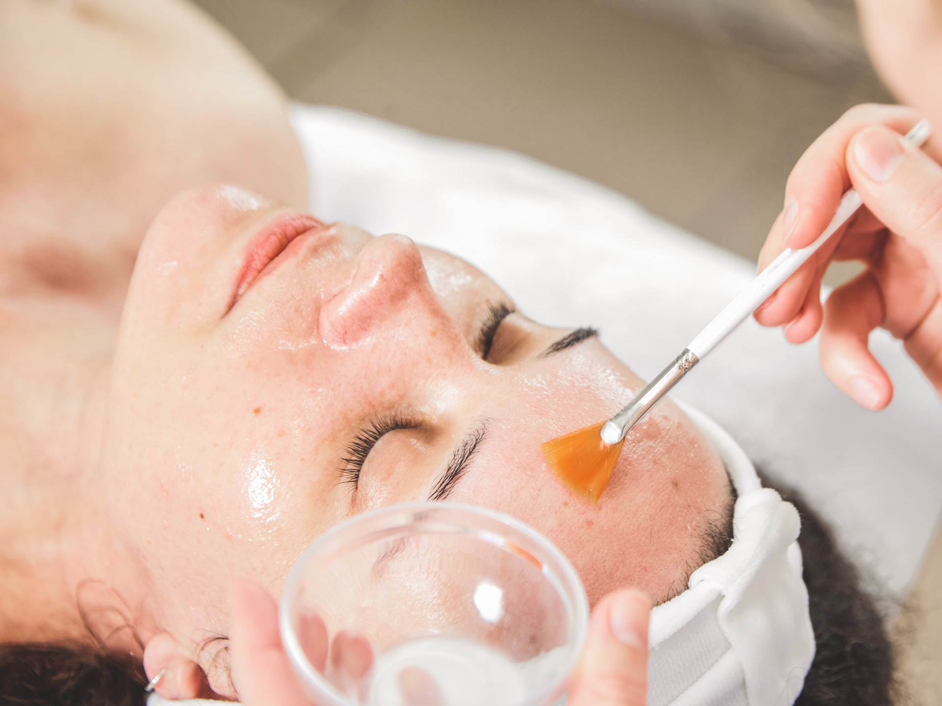 Facial peeling, skin treatment. A dermatologist applies of phytic acid with a white fan brush on female face. A caucasian woman in cosmetic clinic. Cosmetology, facial skin care. Girl in beauty salon